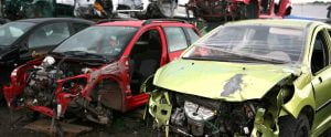 Junk cars sitting in wrecking yard after being removed and stripped for parts