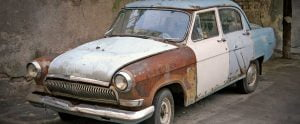 Old vintage car rusting away waiting for old car removal service.