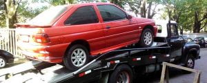 Red car being towed away as part of a car removal service