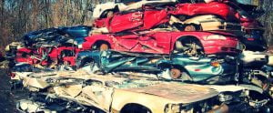 Scrap cars that have been removed, crushed and stacked on top of each other.