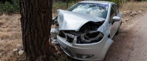 Car with front totally smashed in after crashing into tree